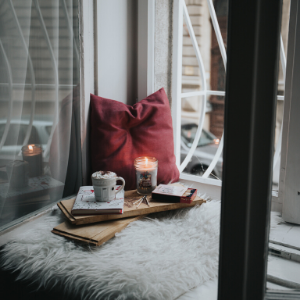 Cozy nook with a candle, pillows, and an open window